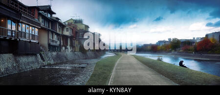 Pathway along the banks of Kamo River in Kyoto, Kamo-gawa, with a young couple sitting by the water. Misty morning - Stock Photo