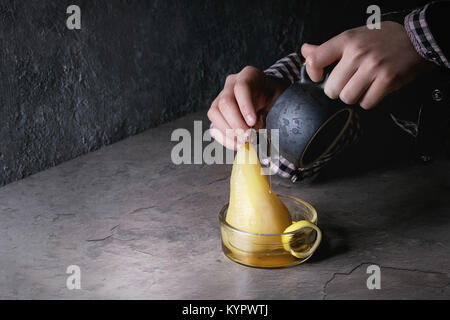 Child hands hold jug and pouring by syrup traditional dessert poached pears in white wine in glass bowls with lemon - Stock Photo