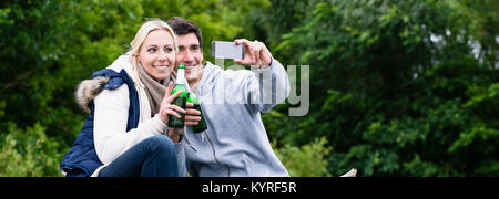 Woman and man drinking beer taking selfie while hiking - Stock Photo