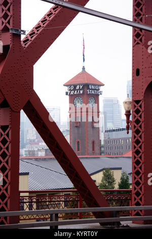 Tower of the train station in Portland with a clock and flag through the farms of Broadway Bridge on Willamette - Stock Photo