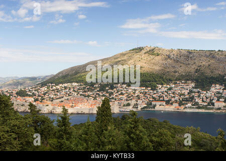 Buildings on the hillside and Mount Srd in Dubrovnik, Croatia, viewed from the lush Lokrum Island on a sunny day. - Stock Photo