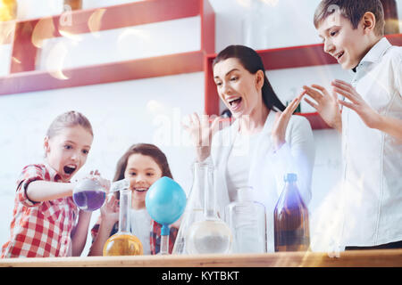 Having fun together. Very emotional group of pupils standing next to their teacher of chemistry and doing practical - Stock Photo