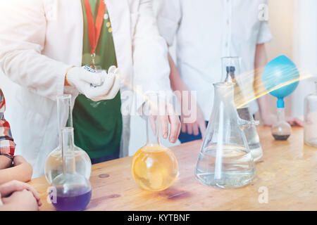 Magical process. Scaled up shot of a group of pupils getting involved in an interesting experiment while all standing - Stock Photo