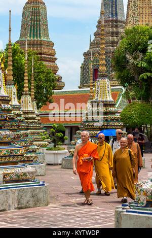 23/06/17 Wat Pho Temple, Bangkok, Thailand. Male and female Monks walk among the Pagodas at the Wat Pho Buddhist - Stock Photo