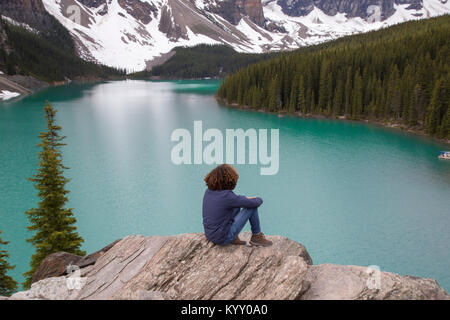High angle view of hiker sitting on rock against Moraine Lake - Stock Photo