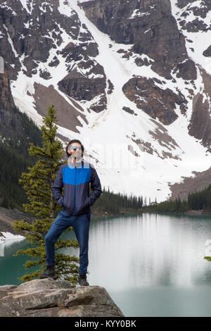 Hiker with hands in pockets standing on rock against Moraine Lake and mountain - Stock Photo