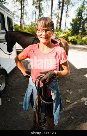 Portrait of happy senior woman with hand on hip holding rope while standing against horse - Stock Photo