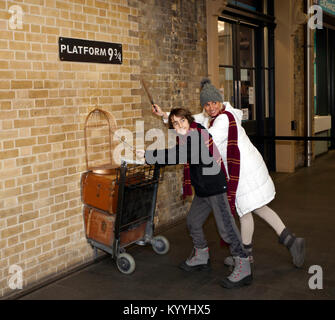 Harry Potter fans pose with Wands and  Gryffindor Scarves by a replica of the trolley entering into platform 9 3/4 - Stock Photo