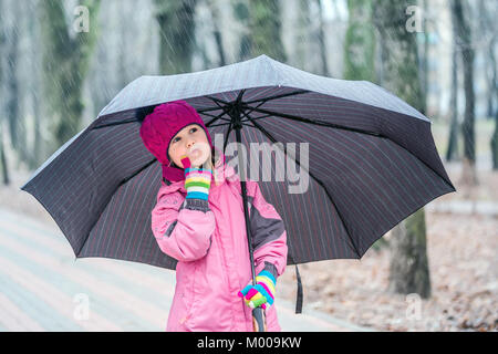 Little cute caucasian girl in hat and jacket walking under umbrella in a city park during rain. - Stock Photo