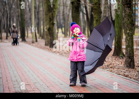 Little cute caucasian girl in hat and jacket walking under umbrella in a city park guess whether it will rain or - Stock Photo