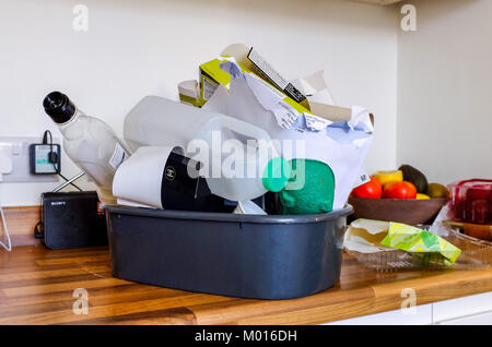 Household domestic waste of cardboard plastic bottles ready for recycling in kitchen - Stock Photo