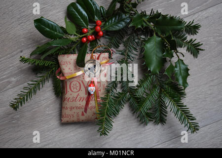 christmas gift with holly branch and wooden background - Stock Photo