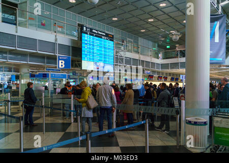 Munich, Germany - October 14, 2017: Passengers stand in front of the departure schedule on an electronic Board at - Stock Photo