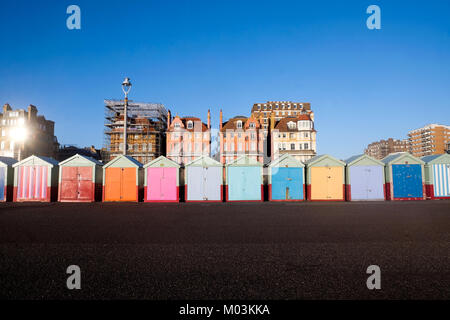 Brighton seafront 13 multi coloured beach huts, on Brighton beach promenade behind is blue sky and 3 victorian buildings, - Stock Photo