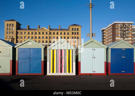 Brighton seafront five beach huts, four with blue and green doors the fifth one in the middle has a multi coloured - Stock Photo