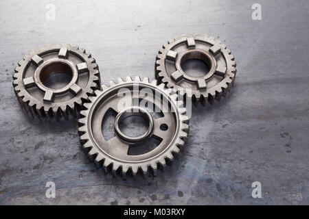 A group of solid metal gears are linked together on a grungy steel background. This set of industrial cog wheels - Stock Photo