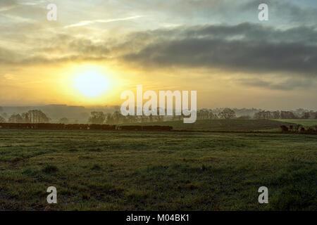 Sunrise on winter morning over foggy fields near Lichfield,Staffordshire,United Kingdom. - Stock Photo