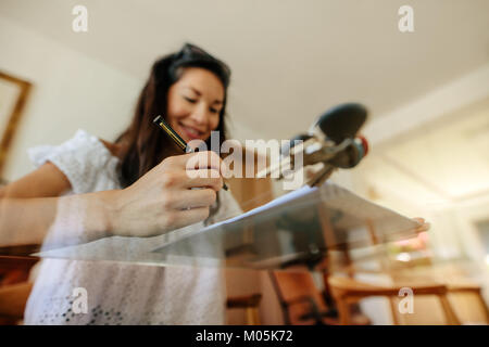 Low angle show of woman buyer reviewing the property documents before signing. Focus on female hand holding pen - Stock Photo