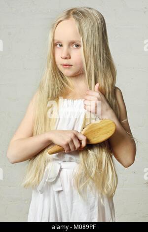 Girl combing hair - Stock Photo