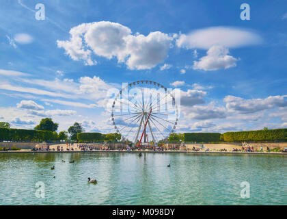 Ferris wheel on the Place de la Concorde from the Tuileries Garden in Paris, France, view from across the fountain, - Stock Photo