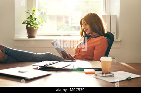 Young African female entrepreneur leaning back in a chair in her home office working online with a digital tablet - Stock Photo