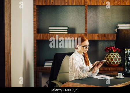 Businesswoman wearing glasses using digital tablet in office - Stock Photo