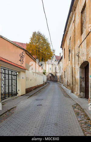 Street view, the narrow Sv Kazimiero Gatve with old dilapidated arch built over the road in the Old Town of Vilnius, - Stock Photo