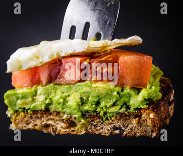Bite sized piece of avocado toast with tomato and a fried egg on a fork.  Isolated on a black background - Stock Photo