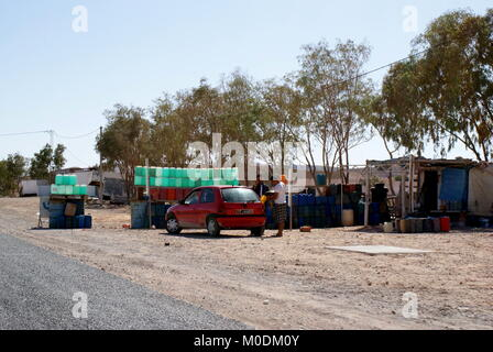 A car fills up with contraband petrol smuggled from Libya on the southern Tunisian roadside - Stock Photo