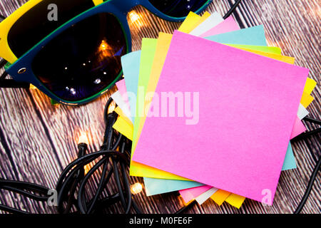 Place for writing sticky note pinned on the wooden background with lights - Stock Photo