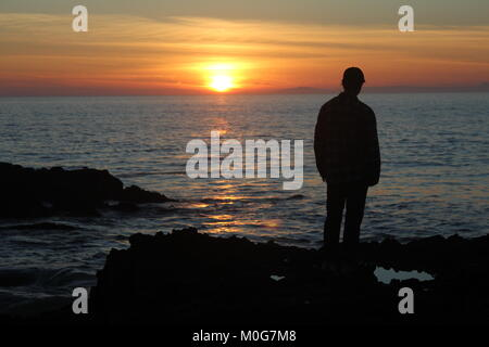 A man staring at a sunset in Laguna Beach. The sun sets over the ocean as a young man watches it. - Stock Photo