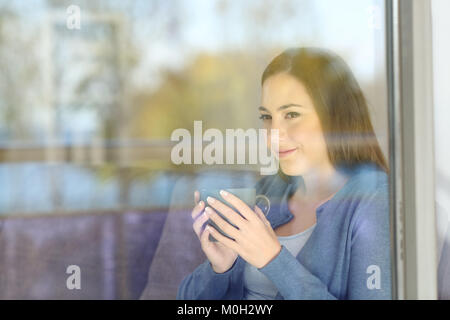 Serious woman looking forward through a window at home with outside reflections on the glass - Stock Photo