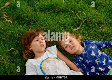 Two young girls lie on grass, portrait, Anderson Park Botanic Gardens, Townsville, Queensland, Australia - Stock Photo