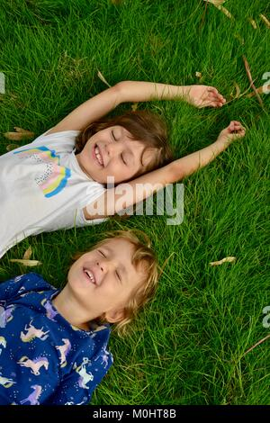 Two young girls lie on grass, portrait, Anderson Park Botanic Gardens, Townsville, Queensland, Australia - Stock Photo
