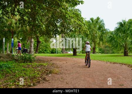 Young girl rides bike on a path with mother and sister walking, Anderson Park Botanic Gardens, Townsville, Queensland, - Stock Photo