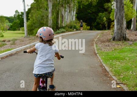 Young girl rides a bike on the road through Anderson Park Botanic Gardens, Townsville, Queensland, Australia - Stock Photo