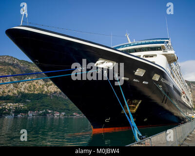 A cruise ship mooring in a port in the Bay of Kotor; Kotor, Montenegro - Stock Photo