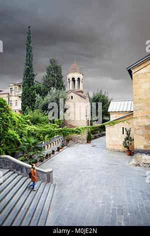 Tourist woman in brown jacket walking down the Old streets near Sioni Cathedral in central Tbilisi, Georgia - Stock Photo