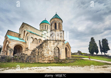Woman walking to the Chapel tower of Bagrati church at overcast sky in Kutaisi, Georgia - Stock Photo