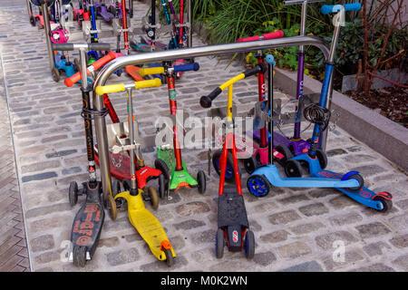 Kids scooters outside nursery school in London, England United Kingdom UK - Stock Photo
