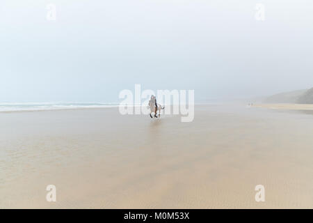 Horse rider riding towards the camera from a distance across low tide. Nice blend on the horizon with the sea mist - Stock Photo