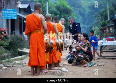 Monks collecting alms in the early morning in Muang Ngoi, Northern Laos - Stock Photo