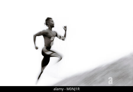 Blur Pan shot of a man running up a hill in the fog. - Stock Photo