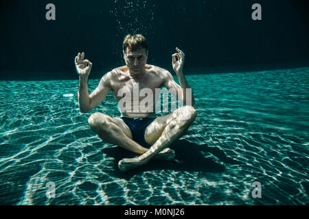 Man sitting in yoga pose underwater in a swimming pool - Stock Photo