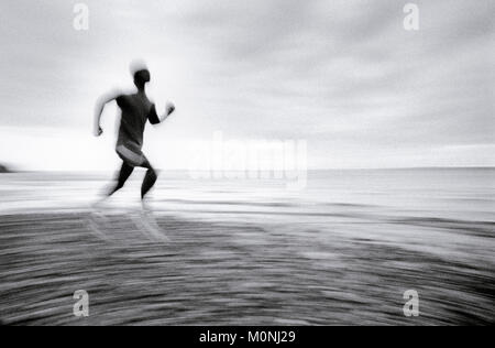 A blurred panning shot of a man running on beach, profile (distorted) - Stock Photo