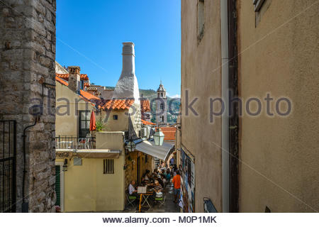Tourists enjoy lunch at a sidewalk cafe restaurant on a narrow alley in old town Dubrovnik, Croatia and a sunny - Stock Photo