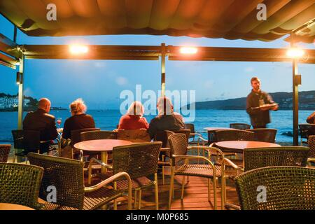 Spain,Girona province,Cadaques,consumers sat under a pergola in the middle of a Café terrace in the face of the - Stock Photo