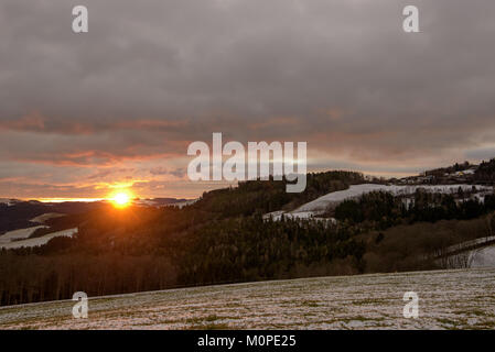 Scenic panoramic color  sunrise over a rural winter countryside in an Austrian hilly landscape with forest, fields - Stock Photo