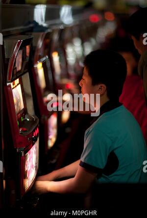 North Korean people playing slot machines in a casino, Pyongan Province, Pyongyang, North Korea - Stock Photo