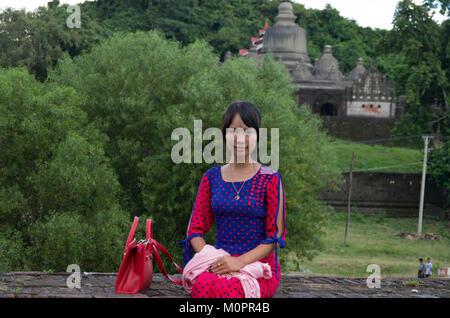 Portrait of a young, pretty woman with a traditional dress sits on a wall in front of the main temple in Mrauk U, - Stock Photo